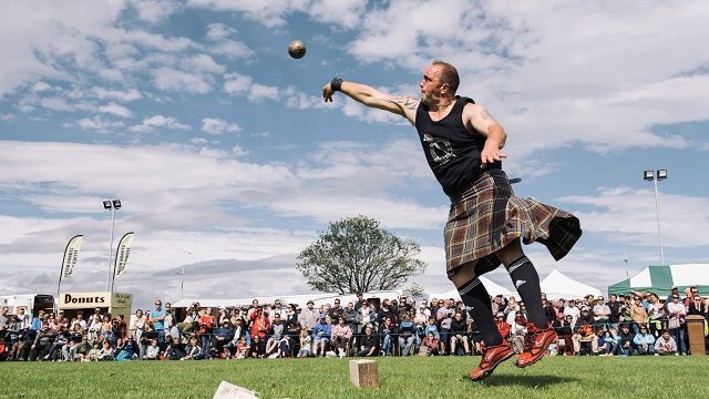 Man in kilt throws shot putt
